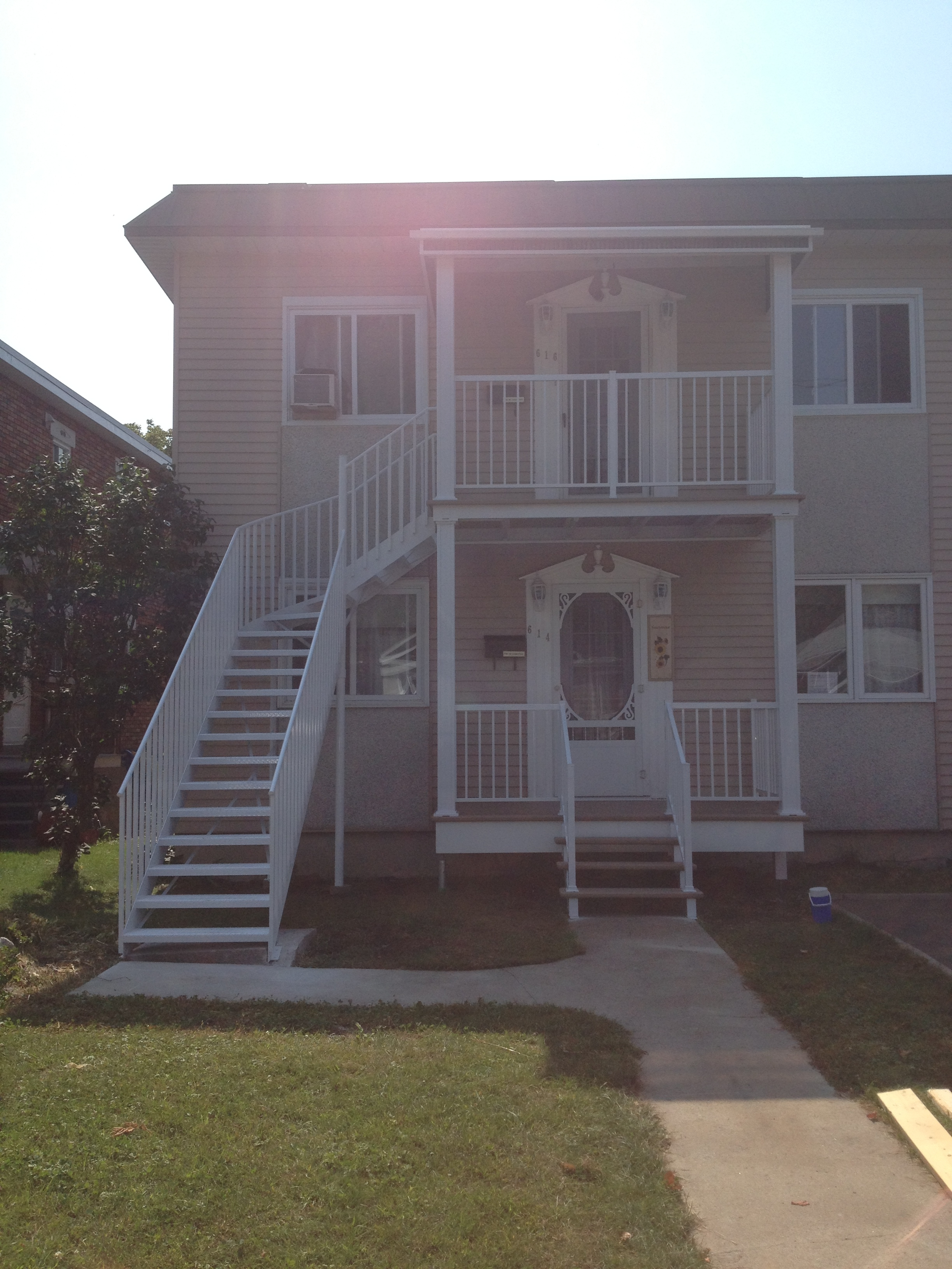 Front of a duplex with staicase, railing and columns2