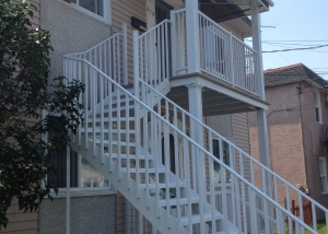 Front of a duplex with staicase, railing and columns